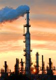 Excess Steam Released at Sunset. At local oil refinery.   Sun is setting between stacks at base of picture Stock Photos