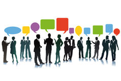 Exchange of business ideas. Silhouetted groups of businesspeople with colorful speech balloons and copy space, white background royalty free illustration