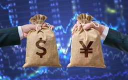 Exchange currency concept. Hands hold bag full of money - Dollar and Yen Stock Photos