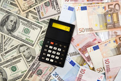 Exchange rate. Dollar and euro banknotes background with calculator displaying exchange rate stock photo