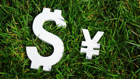 Exchange rate. The yen and the dollar sign on grass. Royalty Free Stock Photography