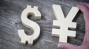 Exchange rating. Dollar and Yen on wooden wall. Exchange rating. Currency sign yen and dollar in male hand royalty free stock image