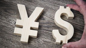 Exchange rating. Yen, Dollar on wooden wall. Exchange rating. Currency sign yen and dollar in male hand royalty free stock image