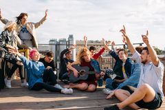 Exchange students singing rooftop together bonding. Carefree exchange students singing together on a rooftop their hands in the air. Bonding, friendship youth royalty free stock image