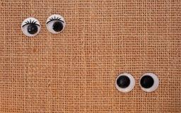 Exchanged glances. Toy eyes on burlap background Stock Photo