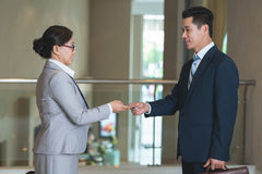Exchanging business contacts. Two smiling Asian colleagues exchanging business contacts Stock Photos