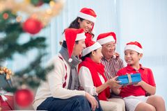 Exchanging Christmas presents. Happy Vietnamese family gathered together to exchange Christmas presents Stock Photo
