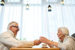Exchanging Christmas Presents. Profile view of surprised senior women wearing knitted sweater sitting at cafe table and exchanging Christmas presents with her Royalty Free Stock Images