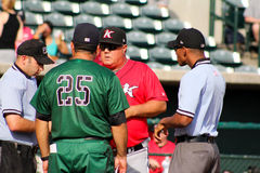 Exchanging Lineups. The managers for the Kannapolis Intimidators (red) and Charleston RiverDogs (green), exchange line-up cards before the start of the game Royalty Free Stock Image