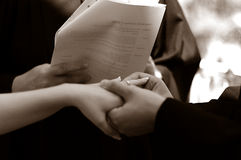 Exchanging rings. Bride and groom exhanging rings Soft focus stock images