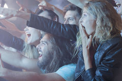 Excidet people stanting at rock concert. Young women standing in a crowd of excited people at a rock concert Royalty Free Stock Photography
