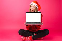 Excité par les bonnes actualités, la femme dans le chapeau du ` s de Santa, tenant un bl image stock