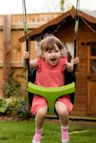 An excitable young girl laughing while playing on the swings stock images