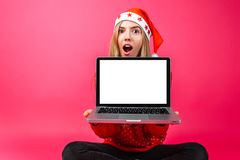 Excitado por la mujer de las buenas noticias, en el sombrero del ` s de Papá Noel, llevando a cabo un espacio en blanco fotografía de archivo
