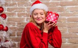 Excitado sobre presente Vestido de la muchacha cerca del árbol de navidad Desempaque del regalo de la Navidad Mujer en caja de re imagen de archivo