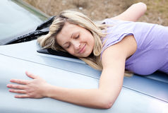Excitador fêmea alegre que abraça seu carro novo Imagens de Stock Royalty Free