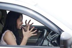 Excitador fêmea irritado que conduz um carro Fotografia de Stock Royalty Free