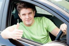 Excitador masculino considerável que senta-se em um carro Fotografia de Stock