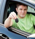 Excitador masculino novo feliz que senta-se no carro azul Fotos de Stock Royalty Free