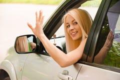 a Excitador-mulher do carro acena para trás imagem de stock royalty free