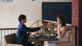Excitan a la muchacha linda sobre propuesta de matrimonio que sonríe y que dice de risa sí mientras que su novio está pidiendo qu almacen de metraje de vídeo