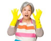 Excite a dona de casa com luvas plásticas e levante a mão acima imagens de stock