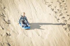 Excite o menino procurando que joga no estilo de vida exterior das dunas de areia imagem de stock