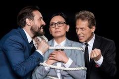 Excited бизнесмены связывая вспугнутую азиатскую коммерсантку с веревочкой Стоковое Изображение RF