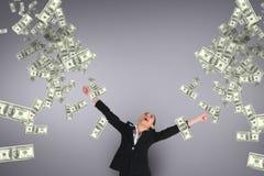 Excited бизнес-леди смотря дождь денег против фиолетовой предпосылки Стоковое Фото