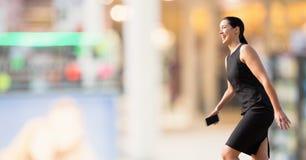 Excited бизнес-леди идя против предпосылки с светами Стоковое Фото