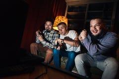 Excited видеоигра игры парней на кресле дома стоковое изображение