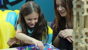 Excited девушка беседует женщина, настольная игра игр, воспитательный процесс акции видеоматериалы