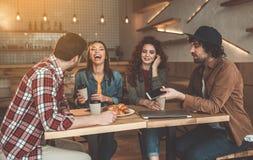 Excited девушки имея потеху с парнями в кафе Стоковые Фото