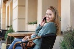 Excited девушка наслаждаясь сообщением на мобильном телефоне Стоковые Фото