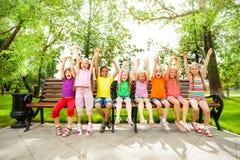 Excited дети с оружиями и сидят в строке на стенде Стоковое Изображение