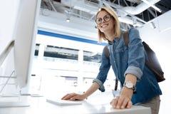 Excited женский покупатель смотря экран компьютера на магазине Стоковое Изображение