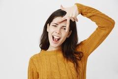 Excited и холодная подруга с прокалыванным показом носа слегка ударила знак победы около лба пока говорящ да, выражающ стоковое фото rf
