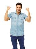 Excited кулаки молодого человека обхватывая стоковые изображения