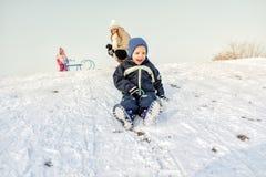 Excited мальчик на снеге tobogganing Стоковая Фотография RF