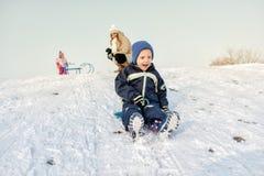 Excited мальчик на снеге tobogganing Стоковые Изображения