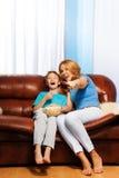 Excited мать указывая на ТВ с смеясь над сыном Стоковые Изображения RF