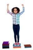 Excited милый ребенок школьного возраста стоя на книгах Стоковые Фото