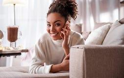 Excited молодая женщина говоря на мобильном телефоне дома Стоковые Фотографии RF