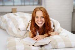 Excited молодая женщина ослабляя в кровати с книгой Стоковая Фотография