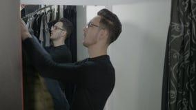 Excited молодой бизнесмен пробуя на одеждах в примерочной для его последняя дата с женщиной - видеоматериал