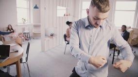 Excited молодой счастливый кавказский бизнесмен празднуя успех с танцем потехи придурковатым в современном здоровом замедленном д видеоматериал