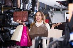 Excited молодая женщина выбирая новую сумку стоковые изображения
