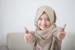 Excited молодая женщина с hijab усмехаясь к камере и показывая thu Стоковое фото RF