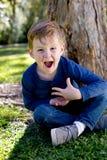 Excited молодое усаживание мальчика пересекло шагающее против ствола дерева в p Стоковое Изображение