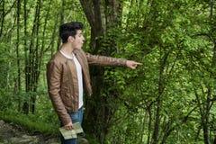 Excited молодой человек с картой указывая в лес Стоковая Фотография